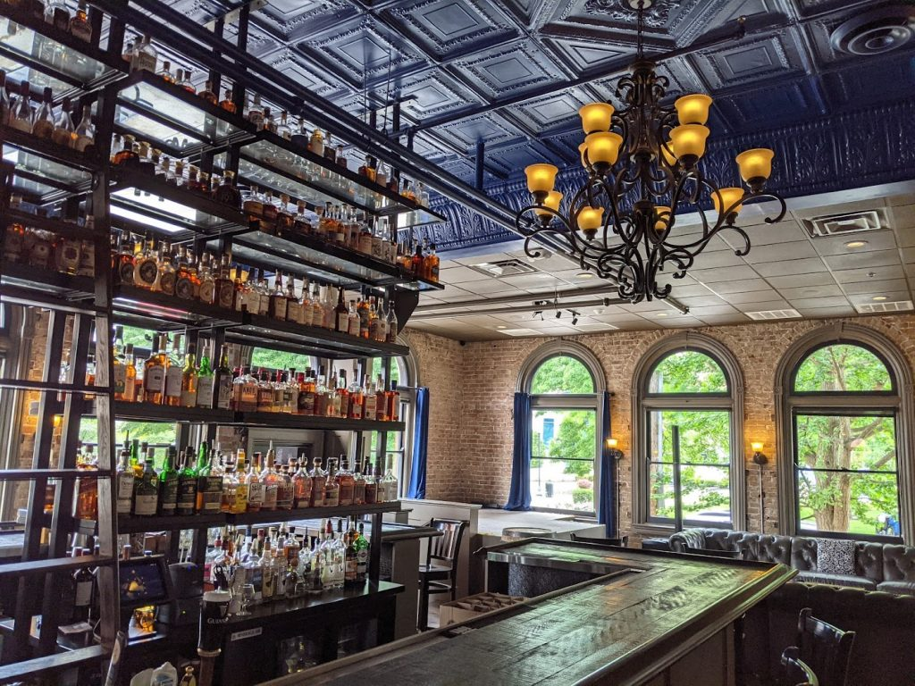 Long wooden bar with shelves of 500 bourbons in the center at Smoke Justis in Covington, Ky.
